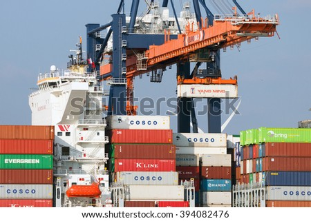 ROTTERDAM - MAR 16, 2016: Crane operator placing a container in a cargo ship the Port of Rotterdam. - stock photo