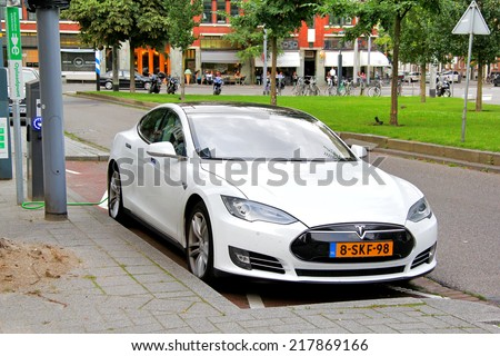 ROTTERDAM, NETHERLANDS - AUGUST 9, 2014: Modern electric car Tesla Model S near a charger at the city street. - stock photo