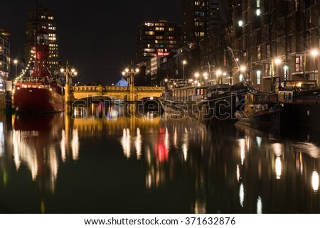 ROTTERDAM, NETHERLANDS - JANUARY 20, 2016: Rotterdam Cityscape with old bridge and boats. Rotterdam is a city defined by modern architecture, with very few old parts. - stock photo