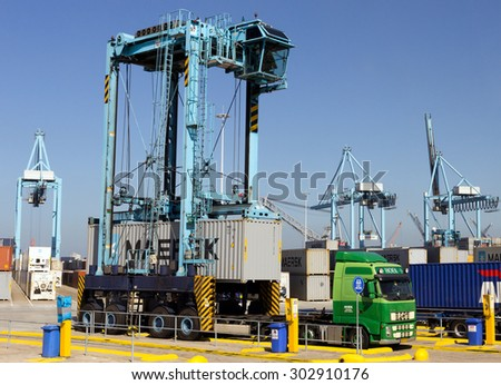 ROTTERDAM, NETHERLANDS - SEP 7, 2012: A Straddle carrier adding a container on the trailer of a waiting truck. - stock photo