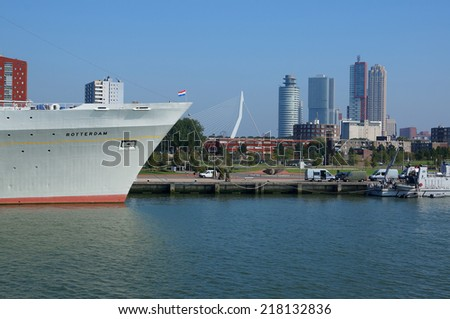 ROTTERDAM, NETHERLANDS - SEPTEMBER 17: Harborside view with SS Rotterdam in the foreground and Rotterdam skyline including Erasmus Bridge in the background on September 17, 2014 in Rotterdam. - stock photo