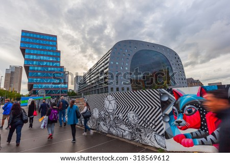 ROTTERDAM, NETHERLANDS - SEPTEMBER 03, 2015: modern market hall in Rotterdam at dawn. It was opened Oct 1, 2014 by Queen Maxima, designed by architect firm MVRDV. With unidentified people - stock photo