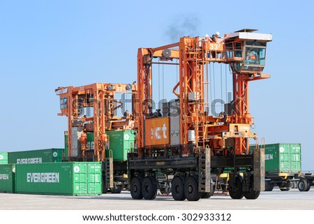 ROTTERDAM, NETHERLANDS - SEPTEMBER 8, 2013: Straddle carrier moving a shipping container in the Port of Rotterdam. The port is the largest in Europe and facilitate the needs of a hinterland with 40,000,000 consumers.  - stock photo