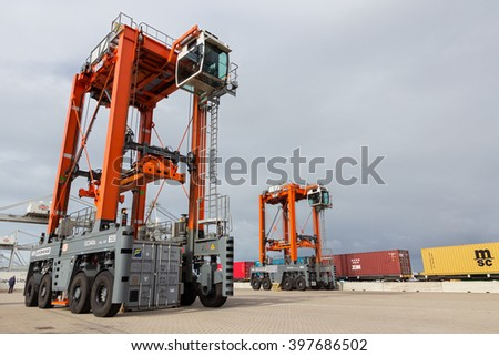 ROTTERDAM - SEP 6, 2015: Straddle carrier moving a container in a container terminal in the Port of Rotterdam - stock photo