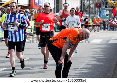 ROTTERDAM, THE NETHERLANDS - APRIL 14 : Exhausted runner giving up during the Annual Fortis Rotterdam Marathon. Runners on the city streets on April 14, 2013 in Rotterdam, The Netherlands. - stock photo