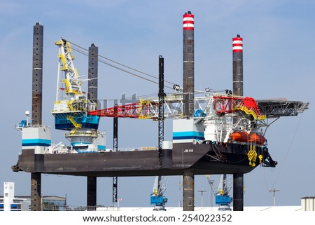 ROTTERDAM, THE NETHERLANDS - AUG 1, 2014: Self Elevating Platform JB-118 docked in the Port of Rotterdam. The rig is build in 2013 and owned by Dutch company Jack-Up Barge - stock photo