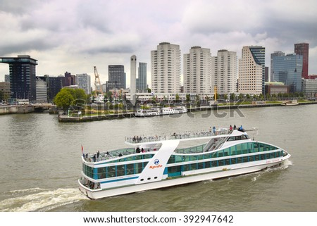 ROTTERDAM, THE NETHERLANDS - 18 AUGUST: View from Erasmus bridge on skyline of Rotterdam with a cruise boat, river Maas in Rotterdam, Netherlands on August 18,2015. - stock photo
