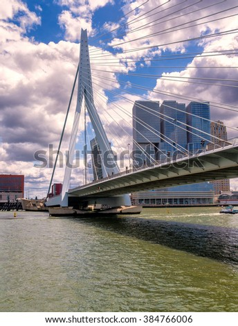 Rotterdam, the Netherlands, May 26, 2015: Erasmus suspension bridge over the Meuse river against a beautiful half cloudy sky with the 'Rotterdam' skyscraper in the background' - stock photo