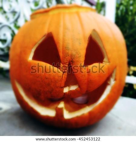Rotting halloween jackolantern pumpkin on a doorstep, filtered effect - stock photo