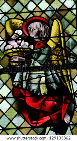 ROUEN - FEBRUARY 10: Angel with a Eucharist on a stained glass in the cathedral of Rouen, France, on February 10, 2013. - stock photo