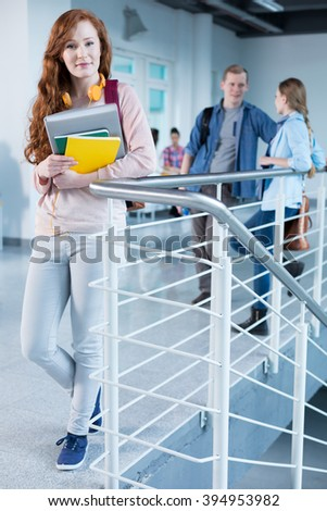 Rouge, academic girl holding her notes, standing against railing in college building - stock photo