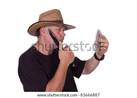 rough and tough cowboy shaving with his knife, looking into a hand mirror, isolated on white