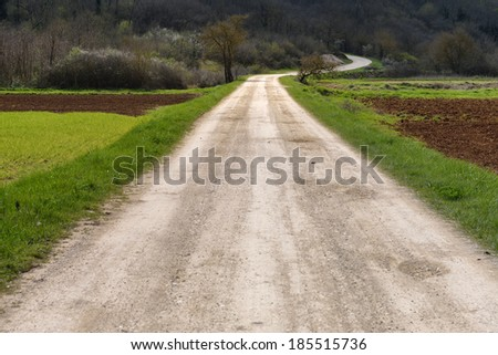 Rough gravel road in the countryside leading far into distance, ending with a curve. - stock photo