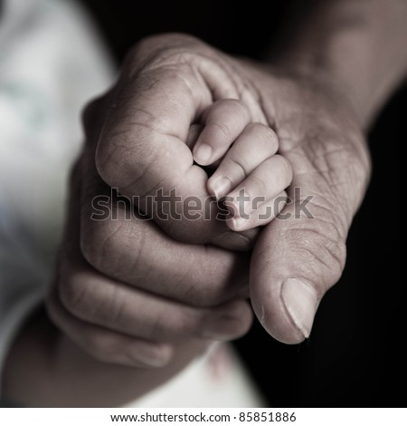 Rough hand holding babyhand - stock photo