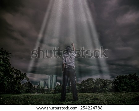 Rough illustration of a man challenging the sky with light shine through the thick clouds in rough-heavy-grain-grunge concept  - stock photo