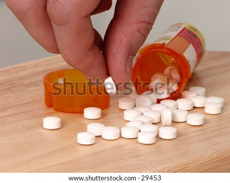 Rough man's hand picking up a prescription pill. - stock photo