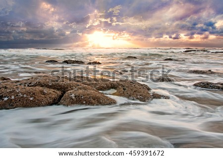 Rough ocean water moving swiftly over jagged rocks and sand. - stock photo