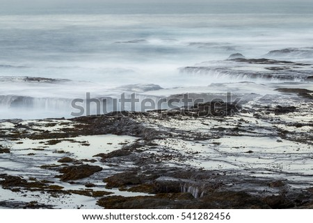 rough seas captured with a slow shutter speed creating a relaxing scene with water flowing over the lava rock with a smooth motion effect