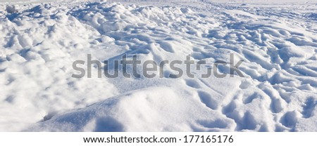 Rough snow surface with snowdrifts, traces and footprints under bright sunlight - stock photo