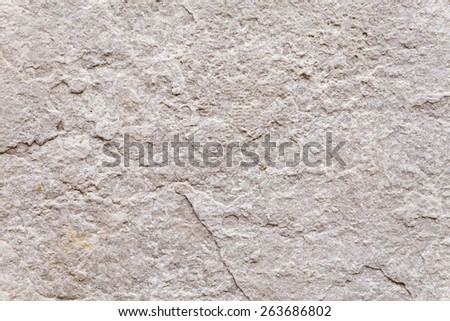Rough surface texture of a weathered block of stone set into the exterior wall of an ancient building. Flat background for two-dimensional spatial compositions. Close up shot outdoors on a tripod.