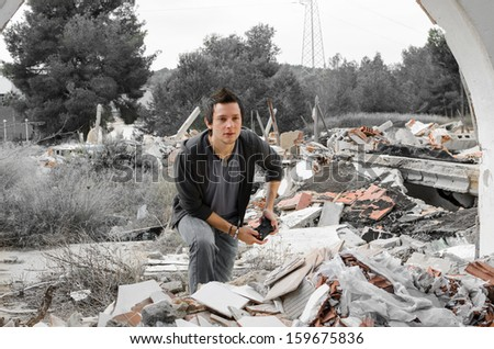 Rough times, a concept: guy playing games in gloomy surroundings - stock photo