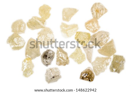 Rough, uncut Diamonds in several colors. - stock photo