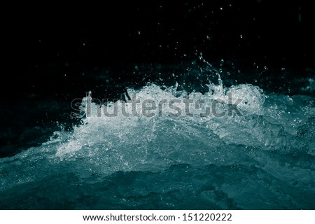 rough water on a black background - stock photo
