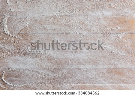 Rough wooden rectangular used cutting board background with flour directly from above closeup - stock photo