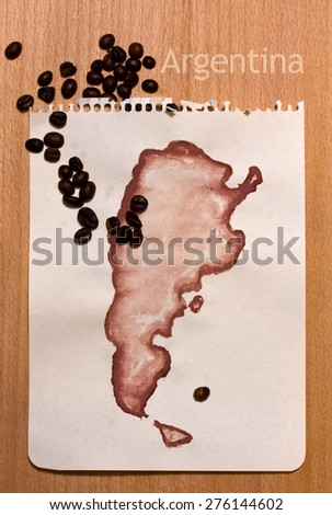 Roughly drawn on the sheet of paper with gouache map of Argentina and coffee beans on it - stock photo