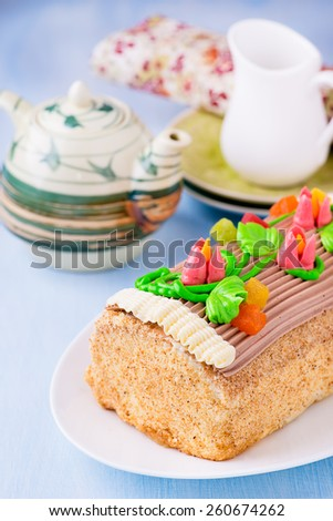 Roulade cake, decorated with colourful buttercream flowers. Yule Log Cake over light blue background. Selective focus - stock photo