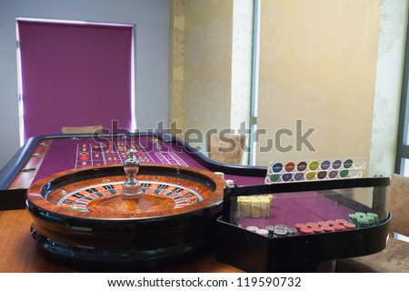 Roulette table and wheel in casino - stock photo