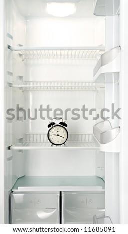 Round alarm clock in an empty refrigerator - stock photo