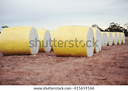 Round bales of harvested cotton wrapped in yellow plastic in Oakey, Queensland. - stock photo