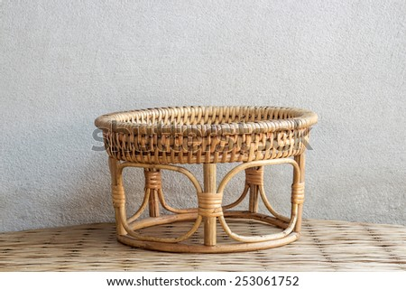 round bamboo weave  tray on mat weave and concrete wall background - stock photo