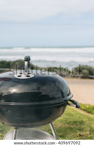 round bbq with lid by the ocean - stock photo