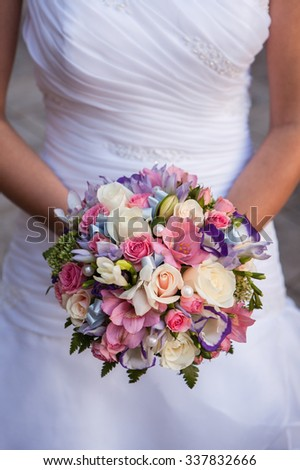round bouquet with white roses, freesia and pearls in the hands of the bride
