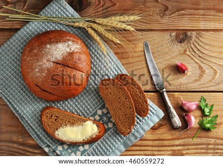 round bread and cut into cutters. bread and butter and wheat ears on wooden background in rustic style. the view from the top