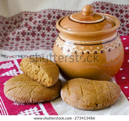 round bread cakes made of rye flour, clay jug on the table