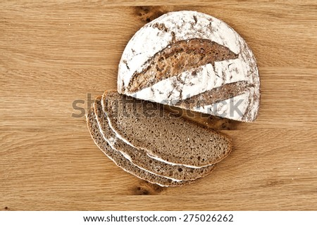 Round bread on a rustic wooden background - stock photo
