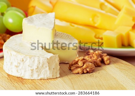 Round camembert and smoked cheese, walnuts with grapes on the wooden board