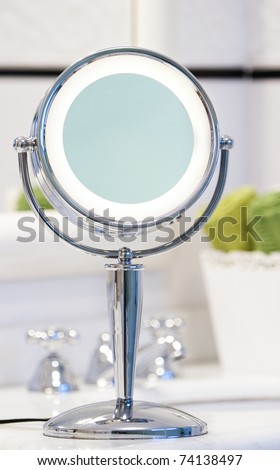 Round chrome lighted makeup mirror in bathroom. Green towels in the background. - stock photo