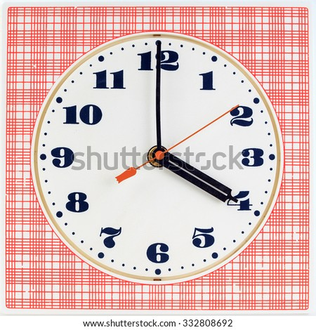 Round clock face on red striped background showing four o'clock - stock photo