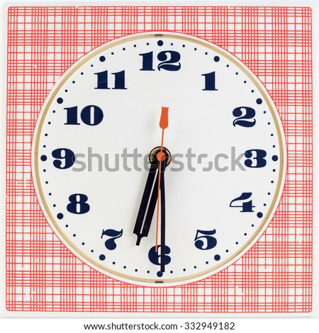 Round clock face on red striped background showing half past six o'clock - stock photo
