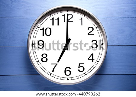 Round clock shows shows at 7 o'clock, clock on blue background - stock photo