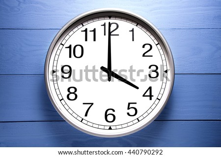 Round clock shows shows at 4 o'clock, clock on blue background - stock photo