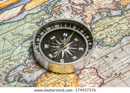 Round compass and ancient map (close up). - stock photo
