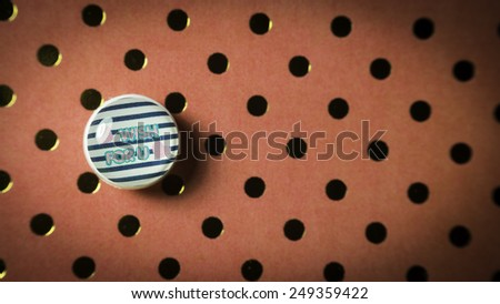 Round cute thumbtack or pushpin for whiteboard, notice board, gift card or special occasions with Wish For You message on polka dot vintage patterns background. Slightly defocused and close-up shot - stock photo