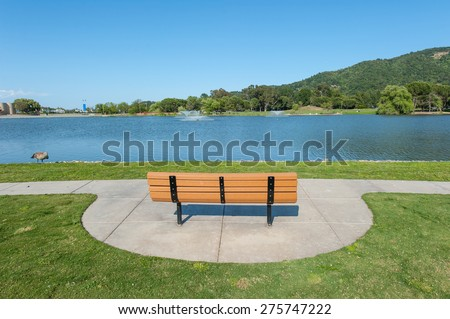 Round grass area near lake with willow tree - stock photo