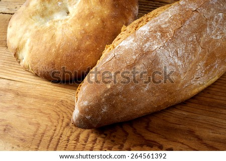Round loaf and bread on wooden table - stock photo