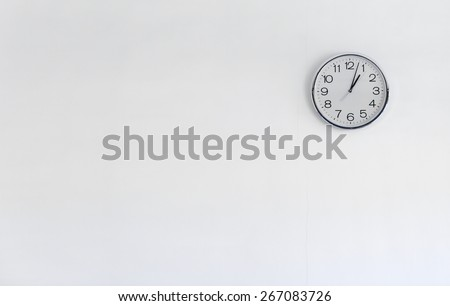 Round metal clock on white wall - stock photo